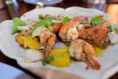 泰国可口的食物 搅动油煎的虾用胡椒和大蒜在白色板材 葱,黑胡椒,香菜,葱混合物  免版税库存照片