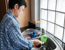 泰国在厨房水槽的妇女清洗的杯子 免版税库存图片