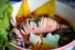 泰国地方食物:海鲜辣面条用乌贼、煮沸的鸡蛋和肉丸 库存照片