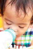 泰国女性从瓶的婴孩饮用奶 免版税库存照片