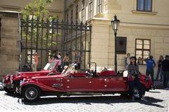 泰国妇女在布拉格城堡附近拍与红色减速火箭的汽车的照片 库存图片