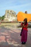 泰国妇女画象和祈祷与斜倚的菩萨 免版税库存照片