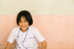 泰国学生坐与微笑的地面在面孔 免版税库存图片