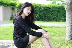 泰国学生青少年的美丽的女孩黑色礼服在公园放松 免版税库存图片