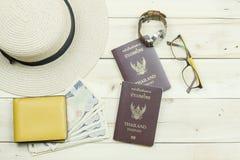 泰国护照、帽子、玻璃、手表、黄色钱包和现金 免版税图库摄影