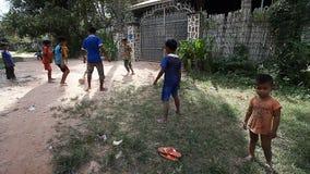 泰国收割,柬埔寨- 2017年1月13日:在路的柬埔寨儿童游戏橄榄球在他们恶劣的村庄 居住  股票录像