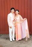 泰国新娘在与开花的诗歌选的泰国婚礼衣服 免版税库存图片