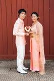 泰国新娘在与开花的诗歌选的泰国婚礼衣服 免版税库存照片