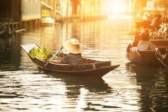 泰国果子卖主在泰国传统浮动市场上的航行木小船 图库摄影