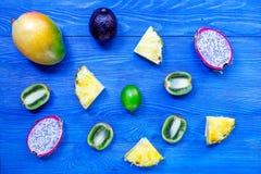 泰国果子片断  Dragonfruit、山竹果树、芒果、猕猴桃和石灰在蓝色木背景顶视图copyspace 库存图片