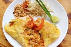 泰国样式煎蛋被包裹的混乱油煎的面条或垫泰国冠上用在白色板材供食的虾 免版税库存图片