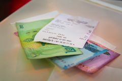 泰国泰铢本国货币与说谎在桌上的现金检查的 在晚餐以后改变THB和检查在咖啡馆 货币 免版税库存照片