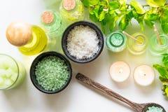 泰国温泉治疗芳香疗法盐和自然绿色糖洗刷并且晃动与绿色兰花花的按摩在木白色机智 图库摄影