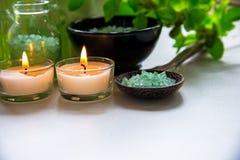 泰国温泉治疗芳香疗法盐和自然绿色糖洗刷并且晃动与绿色兰花花的按摩在木白色机智 免版税库存照片