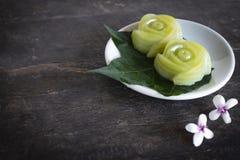 泰国点心分层堆积投入在叶子和白色板材的甜点蛋糕并且有投入此外在桌木头背景的白花 免版税库存图片