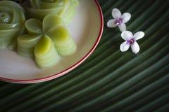 泰国点心分层堆积投入在白色板材的蛋糕有在香蕉叶子背景安置的此外白花的甜点 免版税库存照片