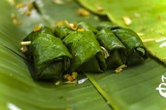 泰国点心糯米、在香蕉叶子包裹的椰奶和香蕉 库存照片