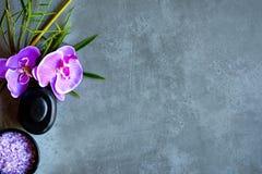 泰国的温泉 设置为按摩治疗的热的石头顶视图和放松与在黑板的紫色兰花有拷贝空间的 免版税图库摄影