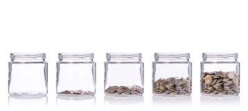 泰国硬币(泰铢)在有另外水平的清楚的玻璃瓶子从le 图库摄影