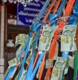泰国纸币垂悬了提供在好运的佛教寺庙 库存图片