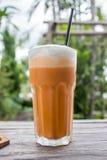 泰国茶frappe用在木桌上的白色奶油或蒸汽牛奶 免版税图库摄影