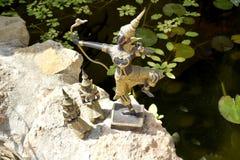 泰国菩萨雕象有射手和两名祈祷的修士的 图库摄影