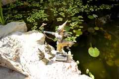 泰国菩萨雕象有射手和两名祈祷的修士的 免版税库存照片