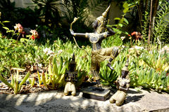 泰国菩萨雕象有射手和两名祈祷的修士的 库存图片