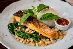 泰国融合食物、油煎的三文鱼和混乱油煎了蘑菇和蓬蒿 库存图片