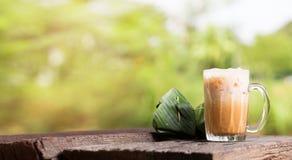 泰国被冰的茶牛奶署名地方街道饮料服务用在木桌上的点心 库存照片