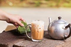 泰国被冰的茶牛奶署名地方街道饮料服务用在木桌上的点心 免版税库存图片