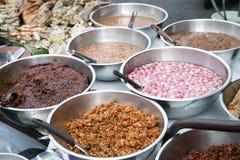 泰国辣椒酱调味汁品种在不锈的碗的出售的在轰隆Lampu市场,曼谷,泰国上 库存照片