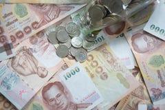 1000泰国钞票和泰国硬币 免版税库存照片