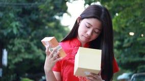 泰国青少年的美丽的女孩用中文穿戴,新年好并且打开箱子礼物,不快乐 影视素材