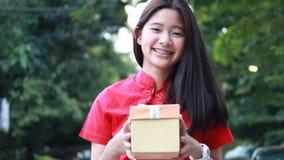 泰国青少年的美丽的女孩用中文穿戴,新年好并且给礼物,放松并且微笑 股票视频