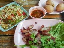 泰国食物样式:& x22; Isan food& x22; 番木瓜沙拉,烤猪肉 免版税库存图片