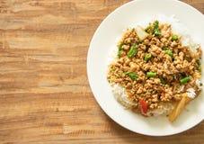 泰国食物,与蓬蒿的混乱油煎的猪肉在木backgroun离开 免版税图库摄影
