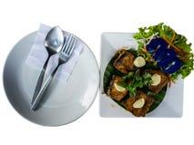 泰国食物,为做准备吃匙子叉子和盘与油煎的鱼和菜 免版税图库摄影