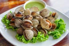 泰国食物,在白色板材的新鲜的鸟蛤在木表上 免版税图库摄影