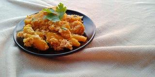 泰国食物:搅动油煎的南瓜用在黑色的盘子的鸡蛋 免版税库存图片