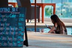 泰国,普吉岛, 2018年3月19日-女孩在水池使用她的智能手机由酒吧 查出的背面图白色 对社会网络的概念依赖性 库存图片