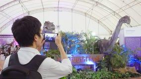 泰国,曼谷, 2015年11月23日 亚裔人在泰国拍与手机的照片在恐龙在曼谷公园 库存照片