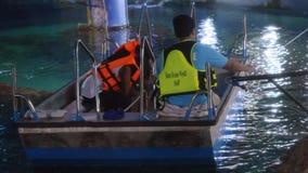 泰国,曼谷, 2015年11月23日 游人在看鱼的水族馆的一条小船游泳通过玻璃 库存照片