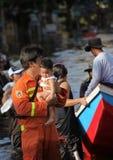 泰国,曼谷- 2011年11月:抱着她的胳膊的救助者一个婴孩,在一次洪水期间在泰国 免版税图库摄影