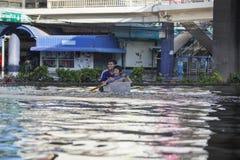 泰国,曼谷- 2011年11月:滑稽的孩子在被充斥的街道上的一个塑料盒游泳 库存照片