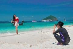 泰国,珊瑚岛, 2018年3月19日-中国年轻人拍摄一件红色女衬衫的女孩在海滩反对热带海 免版税图库摄影