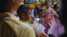 泰国,酸值苏梅岛, 2015年12月5日 拍与执行的孩子MOBIL电话的男孩照片学会舞蹈 免版税图库摄影