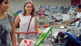 泰国,酸值苏梅岛, 2015年12月7日 走在停车场的美丽的少妇在有充分的购物的超级市场 免版税库存照片