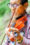 泰国- 2017年弹小提琴的9月10日一个老人在p 免版税库存照片