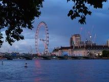 泰晤士河的看法有威斯敏斯特桥梁、伦敦眼和南银行的建筑大厦的在黄昏的 免版税库存图片
